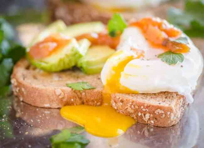 A close up picture of a poached egg spilling it's yolk over the side of a piece of Avocado Toast with Poached Eggs - The Goldilocks Kitchen