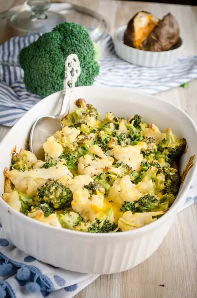 A Cheesy Cauliflower Broccoli Bake with a silver decorative serving spoon - The Goldilocks Kitchen
