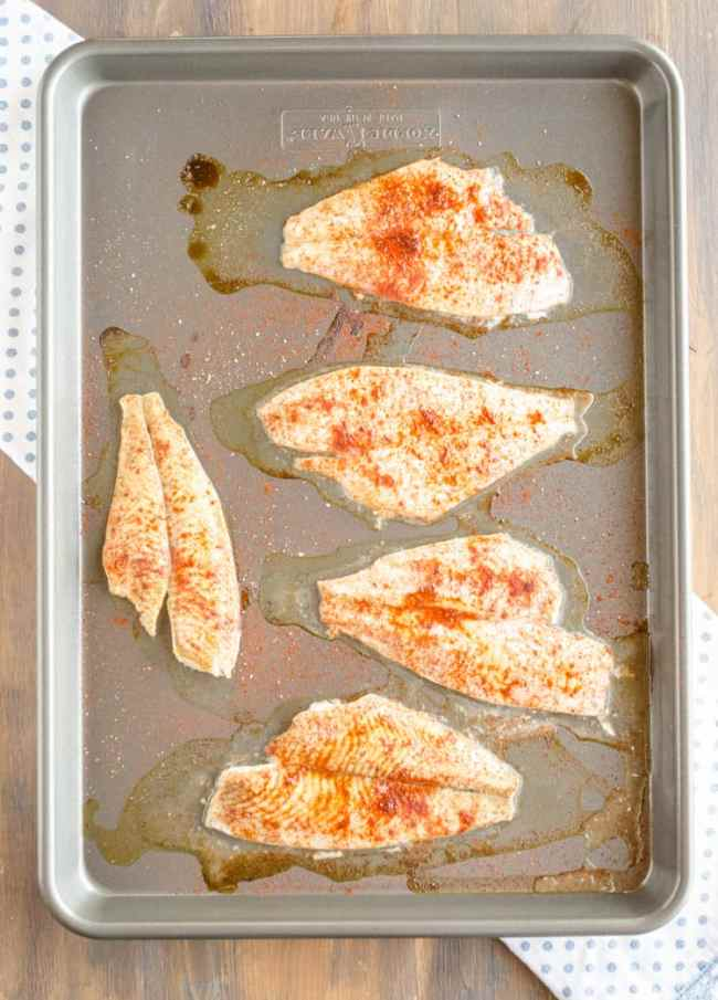 A sheet pan with white fish filets sprinkled with seasonings for Baja Fish Tacos - The Goldilocks Kitchen