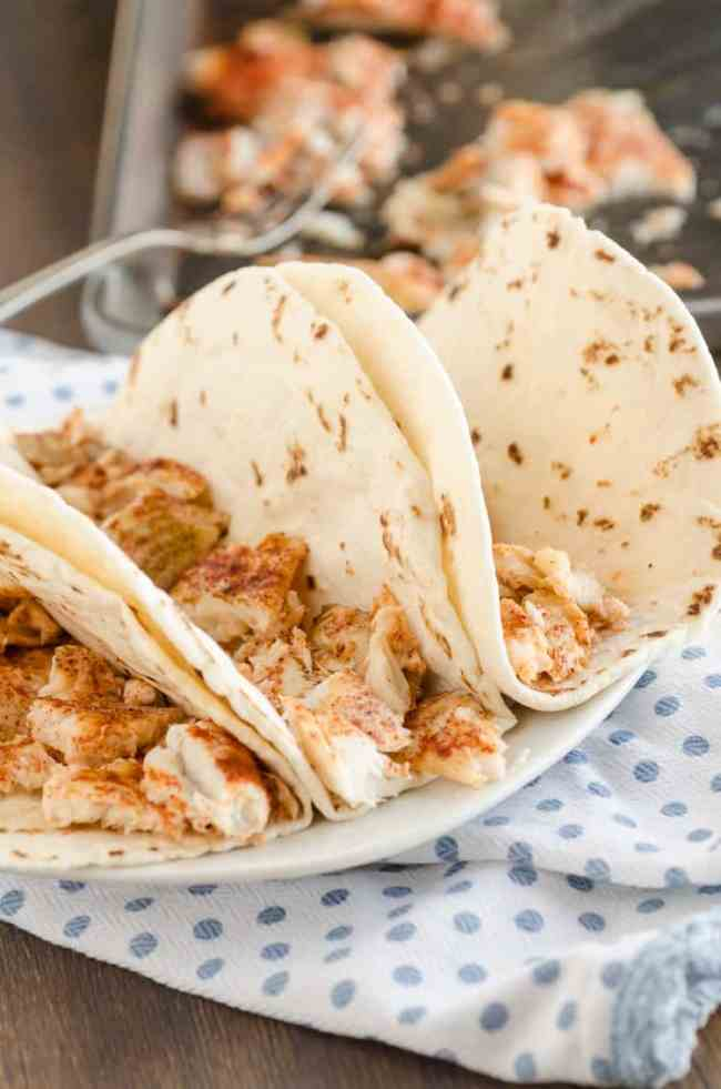 Small flour tortillas  filled with flaky taco seasoned fish for Baja Fish Tacos - The Goldilocks Kitchen