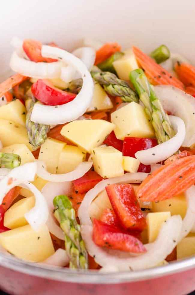 30 Minute Italian Sausage Sheet Pan Dinner close up pic showing raw carrots, potatoes, sausage pieces, red bell pepper, onion slices and asparagus tossed with herbs and oil- The Goldilocks Kitchen