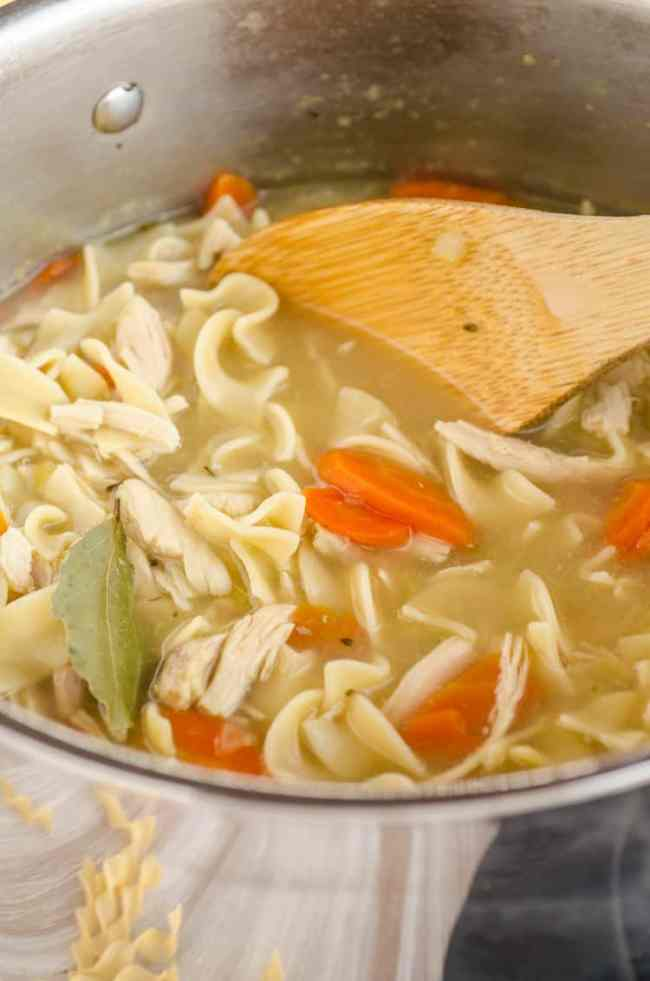Make Ahead Chicken Noodle Soup in a stainless steel pot with carrots and a bay leaf - The Goldilocks Kitchen
