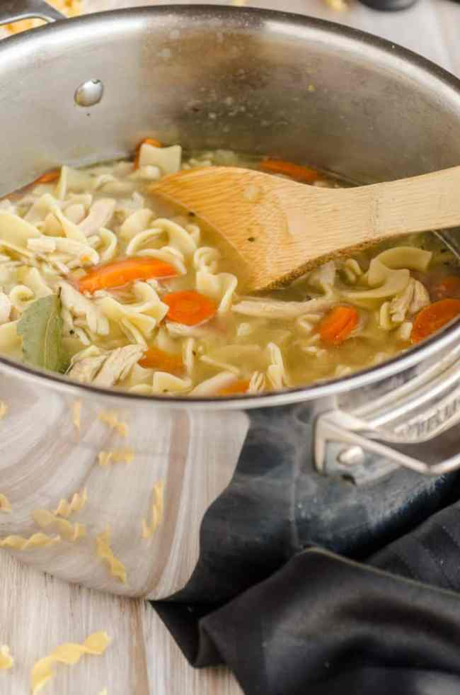 Make Ahead Chicken Noodle Soup in a pot with a large wooden spoon - The Goldilocks Kitchen