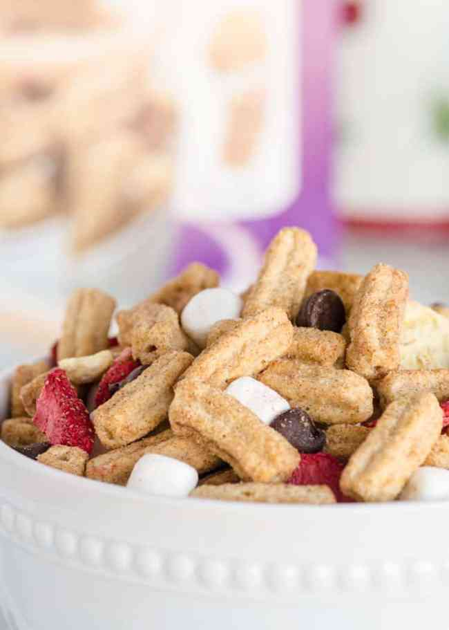 A close up of Churros Snack Mix in a white bowl- The Goldilocks Kitchen
