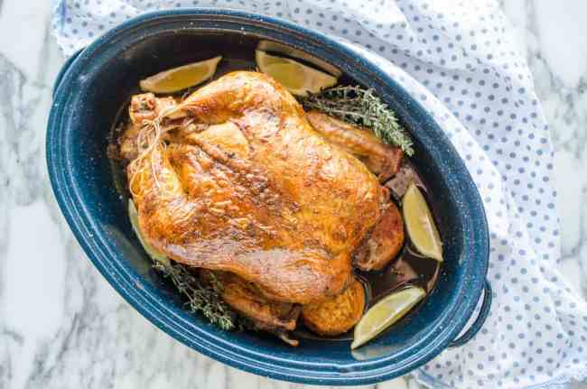 A deep golden colored, freshly roasted chicken sits in a blue/white speckled enamel oval roasting pan for Whole Roasted Chicken and Sweet Potatoes - The Goldilocks Kitchen