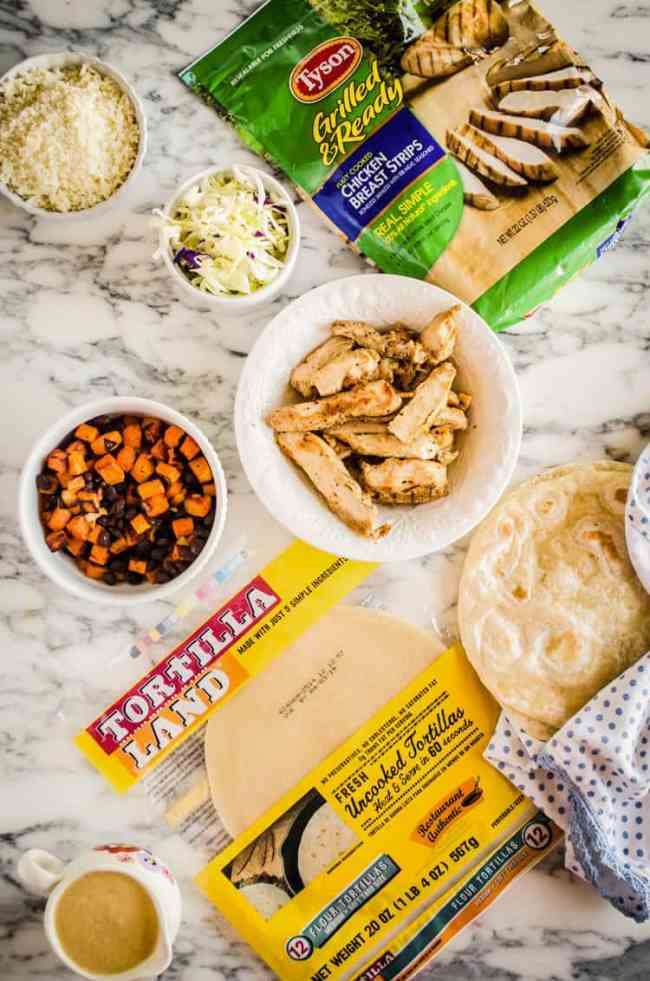 All ingredients to make Grilled Chicken Tacos with Green Chile Cream Sauce spread out on a marble counter - The Goldilocks Kitchen