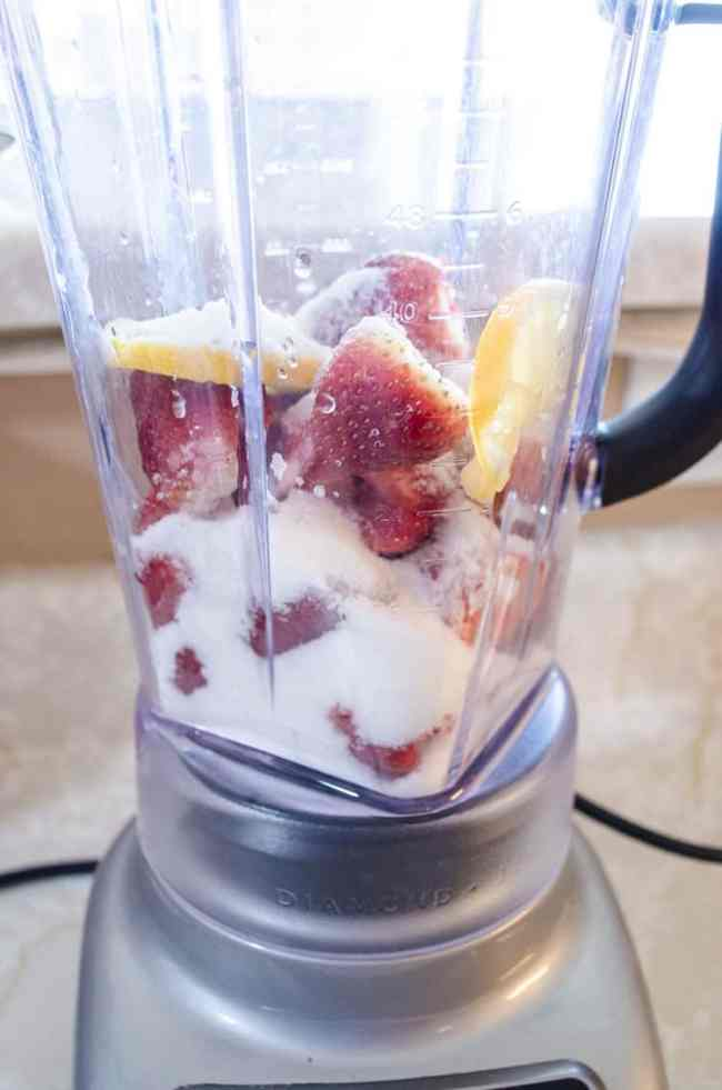 A blender is filled with strawberries, lemon slices and sugar for Fresh Sparkling Strawberry Lemonade - The Goldilocks Kitchen