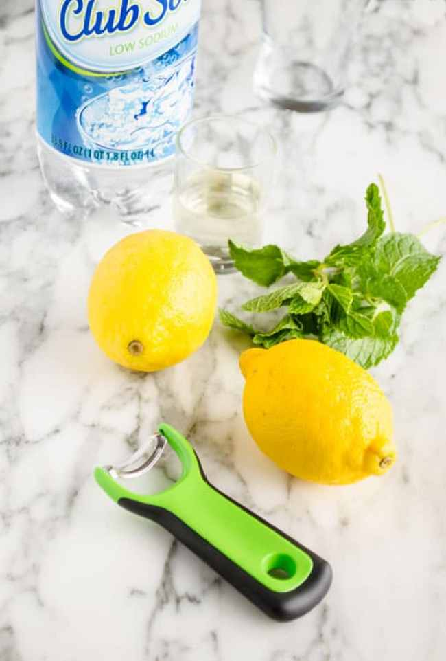 Two lemons, a bottle of club soda, simple syrup, an empty glass, fresh mint and an OXO Citrus Prep Peeler are all you need to make a fresh Lemonade Sparkler - The Goldilocks Kitchen