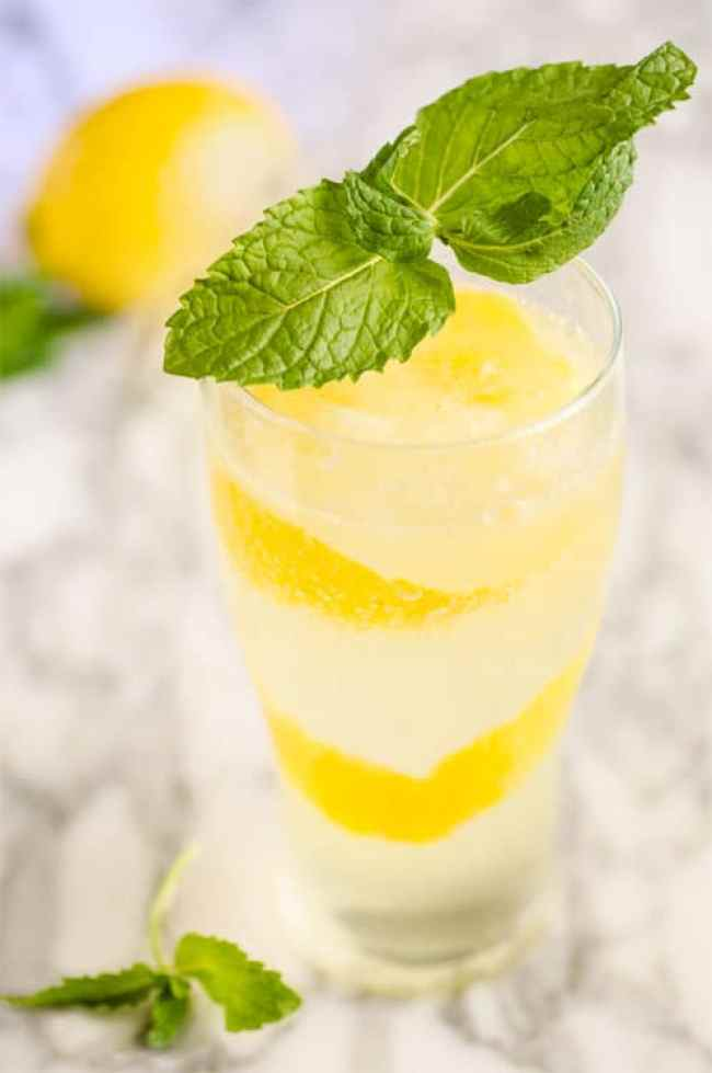 A tall clear Lemonade sparkler drink, garnished with a long thin spiral of lemon zest in the glass and a large sprig of fresh mint. - The Goldilocks Kitchen