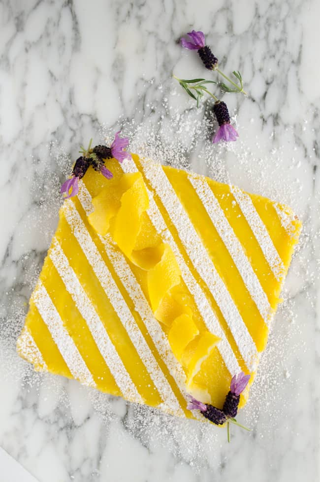 A batch of Goldilocks Kitchen Lemon Bars garnished with stripes of confectioner's sugar, a lemon peel spiral in the center and purple lavender flowers at the corners -The Goldilocks Kitchen