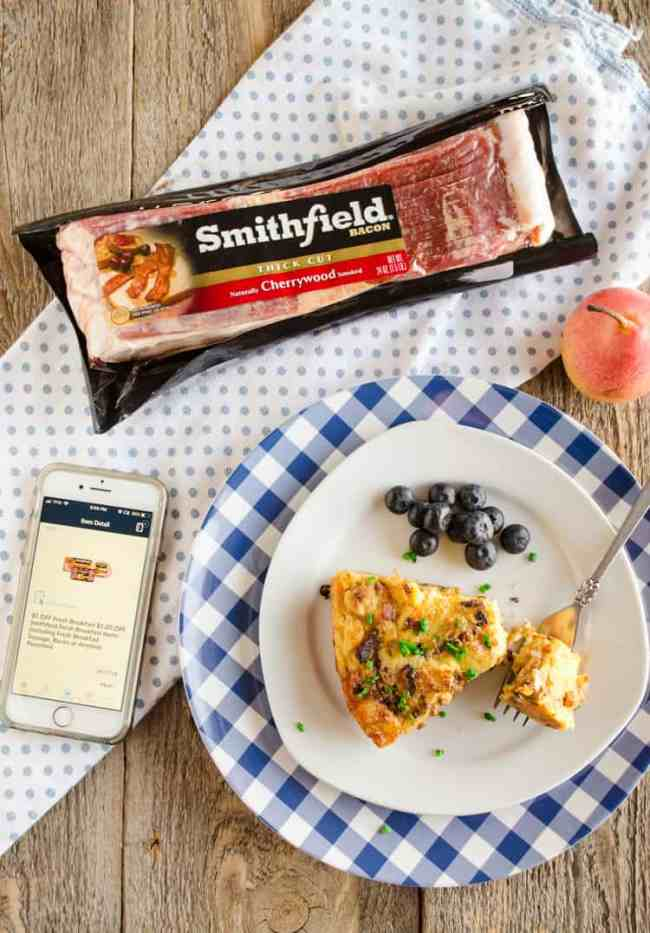 Looking down on a plate with a slice of Bacon Cheddar 30 Minute Skillet Strata next to an iPhone with a coupon displayed next to a package of Smithfield Bacon for Bacon Cheddar 30 Minute Skillet Strata - The Goldilocks Kitchen - The Goldilocks Kitchen