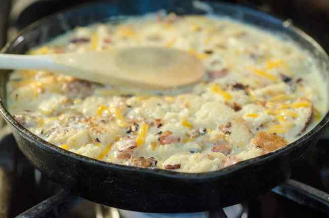 A mixture of uncooked egg, milk, bread, shredded cheddar cheese, chopped bacon and onion in a cast-iron skillet ready to be baked into a Bacon Cheddar 30 Minute Skillet Strata - The Goldilocks Kitchen