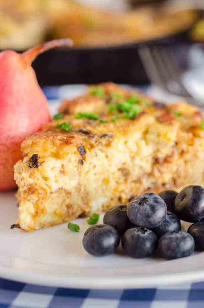 Bacon Cheddar 30 Minute Skillet Strata slice with some blueberries on the side - The Goldilocks Kitchen