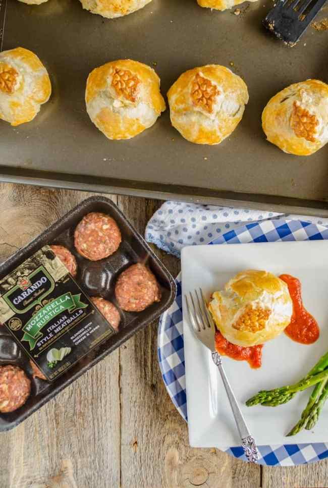 An Easy Meatball Wellington on a plate next to a package of Carando Meatballs. Adjacent is a rimmed baking sheet with more Easy Meatball Wellingtons. - The Goldilocks Kitchen