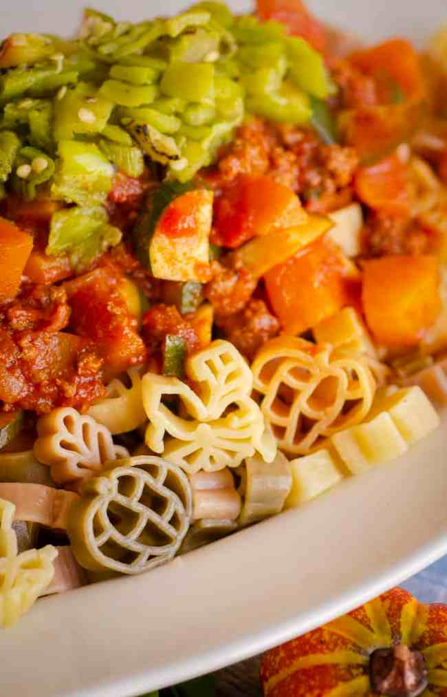 A closeup of Green Chile Squash Goulash showing a hearty texture served over fun multi-colored Autumn-shaped pasta.