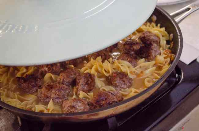 One-Pot Meatball Stroganoff in a large skillet is being covered with a lid to cook the noodles and meatballs together.