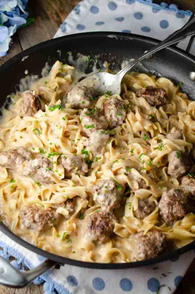 A skillet full of One-Pot Meatball Stroganoff sits on a wooden table with a large decorative serving spoon in it.