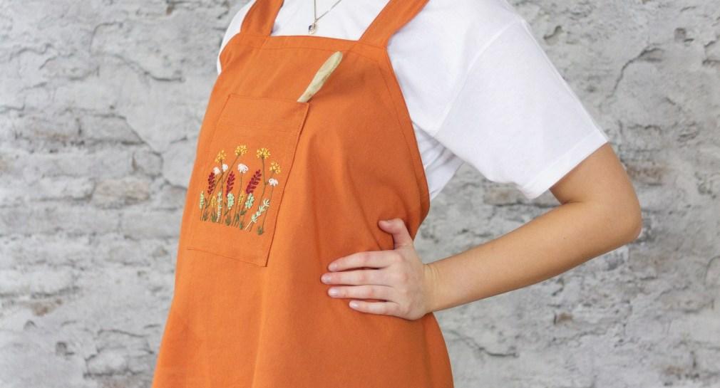 Bloggerin Antonia steht seitlich mit angewinkeltem Arm vor einer grauen Steinwand und trägt die selbst genähte orangene Schürze.