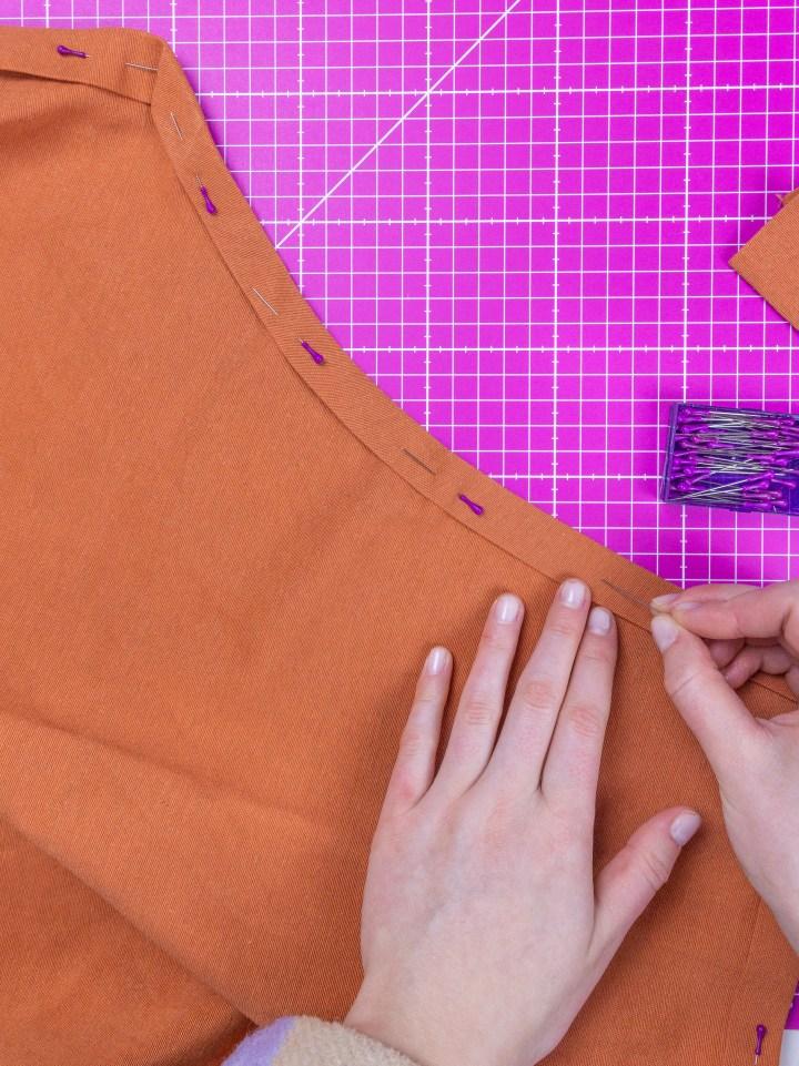 Der abgerundete Rand der Schürze unterhalb der Arme wird zweimal nach innen eingefaltet und mit Stecknadeln abgesteckt.
