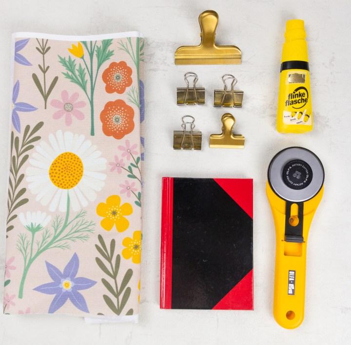 Alle Materialien für das DIY mit Stoff bezogene Notizbuch liegen als Flatlay nebeneinander: Stoff, Klemmen, Notizbuch, Kleber, Rollschneider.