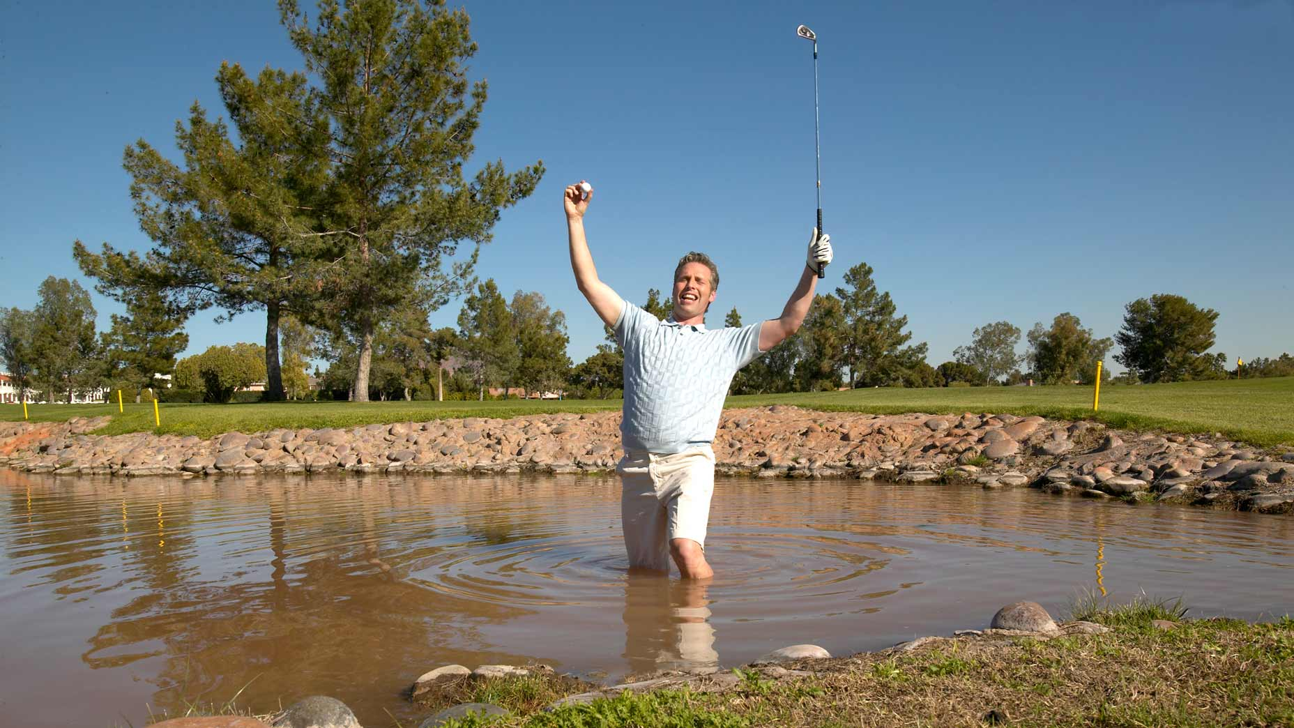 man swims in lake for golf ball