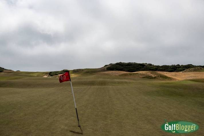 The wind bends the flagstick at Old MacDonald at Bandon Dunes. Notice how there is no visual difference between fairway and green.