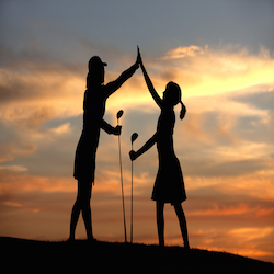 A mother and daughter in silhouette at sunset celebrate with high fives after a good drive.