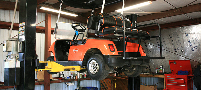 Orange golf cart on repair lift