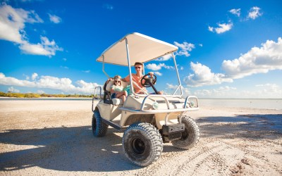 Dad and his two daughters driving golf cart at tropical beach