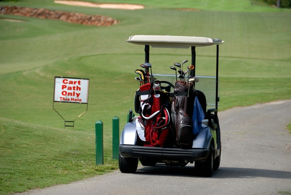 golf cart in the golf course with two bag full of golf clubs