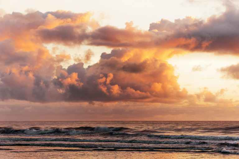 fluffy sunset clouds above waves