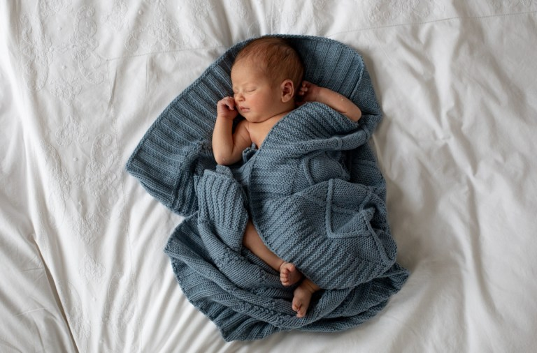newborn wrapped in blanket at home