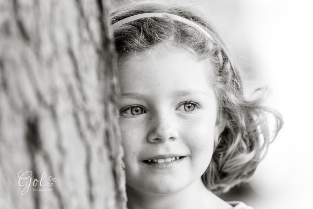 little girl portrait in summer photoshoot by a tree