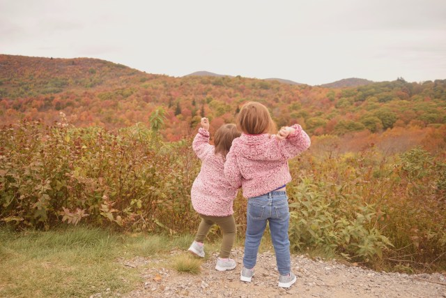 my daughters throwing pebbles over the hill in front of the mountains