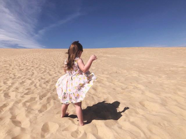 girl standing in dunes at jockeys ridge state park