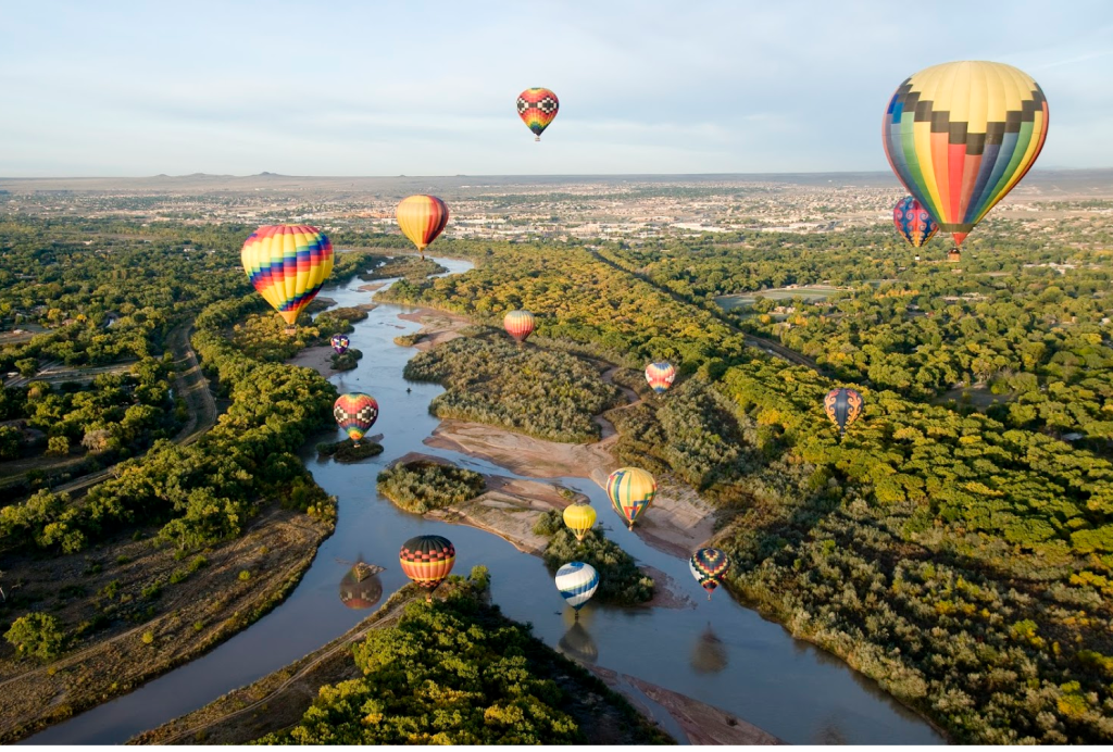 hot air balloon flying above the city and waterway