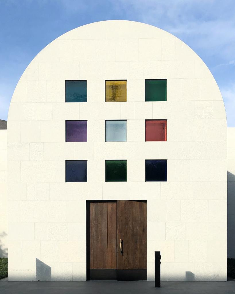 white building with rounded top and colored window glass