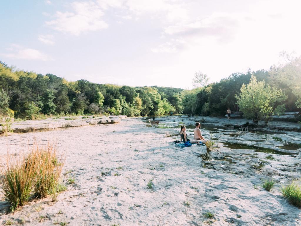 people sitting on edge of swimming hole