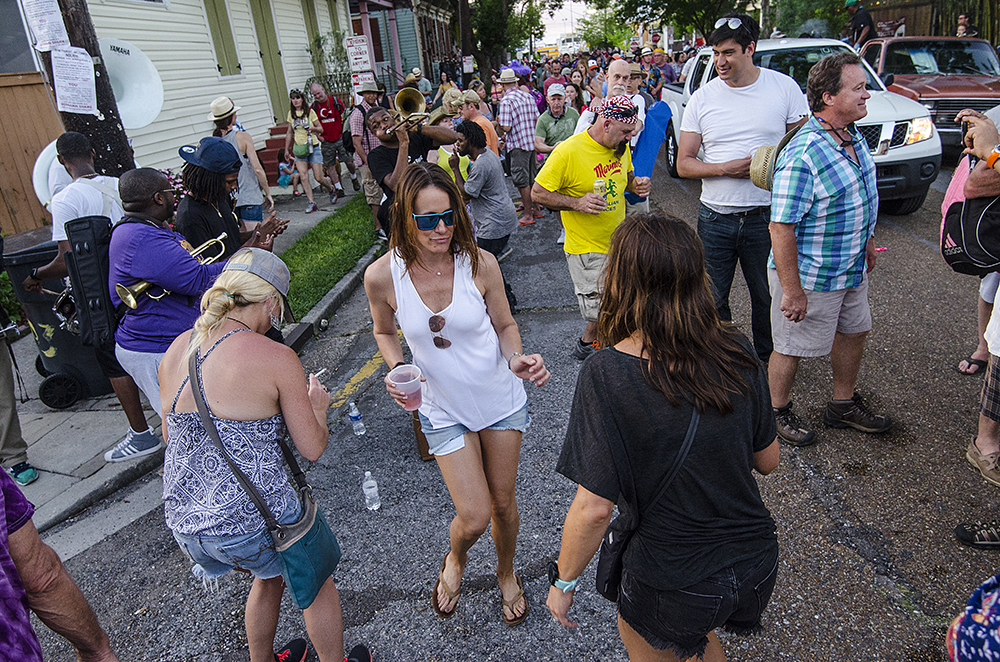 April 22, 2016 - New Orleans, LA: The streets surrounding the Fairgrounds become packed with artists, musicians, and fans following the New Orleans Jazz and Heritage Festival, creating impromptu street parties. In true New Orleanian fashion, attendents leaving the festival showed no signs of stopping while dancing to the music of the New Life Brass Band, who set up shop on the corner of Ponce De Leon and N. Lopez streets. (Photo by Katie Sikora)