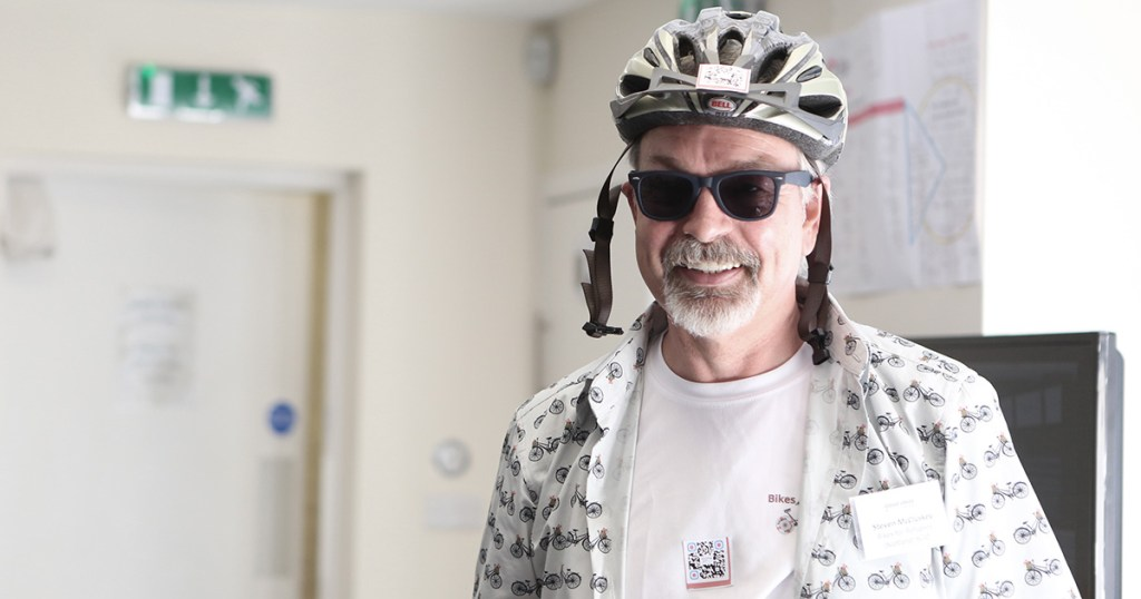 Steven McCluskey, Bikes for Refugees (Scotland) wearing a cycle helmet and sunglasses at the Good Ideas Marketplace