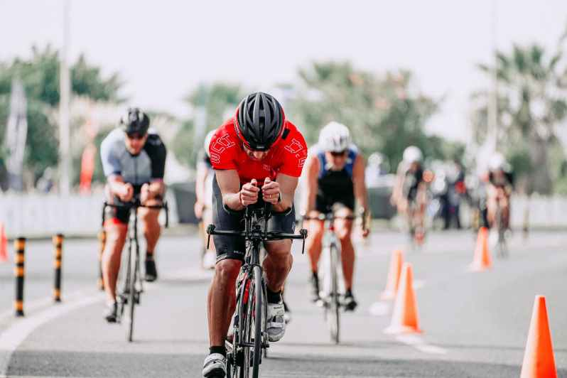 unrecognizable cyclists riding bikes on road during race