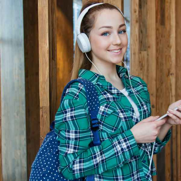 woman in teal white and black plaid dress shirt standing beside brown wall