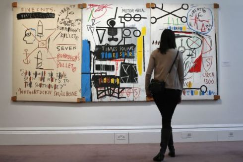 A visitor stands in front of a painting by Jean-Michel Basquiat entitled 'Five Fish Species,' in London, England. (Photo by Dan Kitwood/Getty Images)