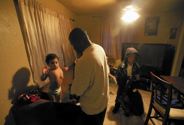 On weekdays, Bryan August-Jones wakes before sunrise in his home in Watts. He gets his three sons dressed, then takes them to the baby sitter and to school. On weekends, they go on bike rides and out to eat. (Mark Boster, Los Angeles Times / December 19, 2013)
