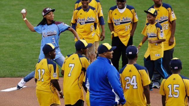 Mo'ne Davis, the first female pitcher in Little League World Series history to pitch a complete-game shutout accompanied by players from the Jackie Robison West Little League team, throws out the ceremonial first pitch before Game 4 of baseball's World Series between the Kansas City Royals and the San Francisco Giants Saturday, Oct. 25, 2014, in San Francisco. (AP Photo/Jeff Chiu)