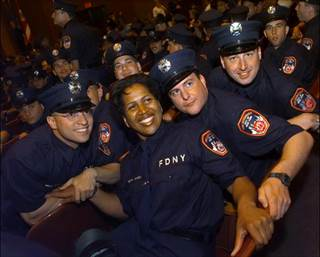 Wilson, seen with fellow graduates at Brooklyn College, was the only woman in her class and the 12th African-American woman to join the FDNY when she entered the department in 1999.  (DAVID HANDSCHUH/NEW YORK DAILY NEWS)