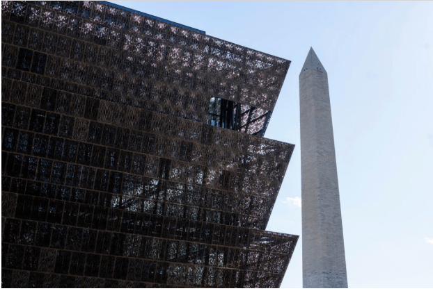 The museum, foreground, was designed by David Adjaye and sits on the National Mall near the Washington Monument, right. (MATT ROTH FOR THE NEW YORK TIMES)