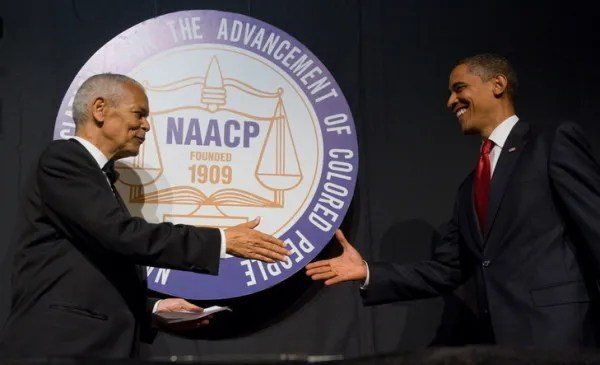 US President Barack Obama shakes hands with former NAACP chairman Julian Bond (L) during the NAACP 100th Anniversary convention in New York, July 16, 2009. (Photo credit SAUL LOEB/AFP/Getty Images)