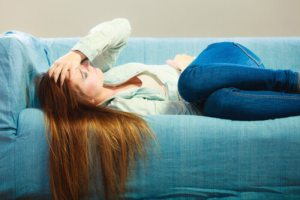 Depressed teenager girl curled up on couch with hand on her head