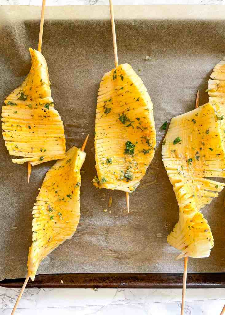 overhead image of 4 accordion potato skewers brushed with garlic herb butter